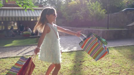 riches : happy childhood, smiling girl enjoying new purchases in paper bags and rotates on green grass outdoors