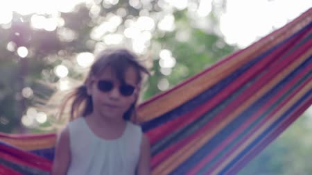 desfocado : smiling child girl into sunglasses swinging in hammock on nature close-up in unfocused Stock Footage