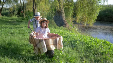 клетчатый : entertainment outdoor, little boy riding girl in wheelbarrow in countryside near the lake
