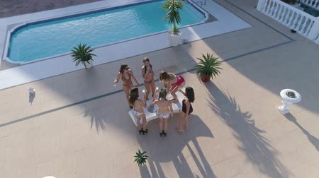 champagne pool : hen-party, cheerful girls into bathing suits are dancing and drinking alcohol near pool at Expensive holiday in summer, aerial view