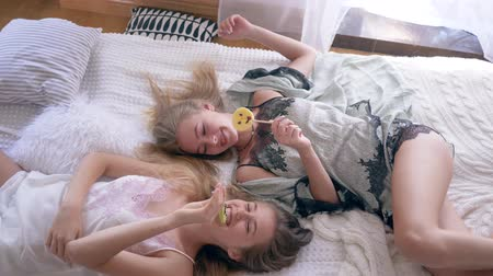 леденец : cozy atmosphere, sisters in silk sleepwears eat sweet lollipops and talk lying on the bed at home Стоковые видеозаписи