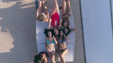 champagne pool : summer resort, group of attractive girls into bathing suit lie down take turns on deck chair near Swimming-pool in drone view