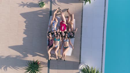 champagne pool : sunbathing, happy Friends girls into Swimsuit and sunglasses relaxing on lounger near Poolside at luxurious holiday in view from above Stock Footage