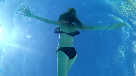 dupa : underwater bottom view on Slender sexy female with beautiful ass into bathing suit relaxes in Poolside Wideo