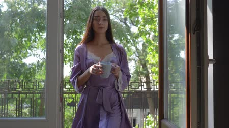 encantador : girl in bathrobe enjoy fresh air and nice look on the balcony with a cup and then come into the bedroom Stock Footage