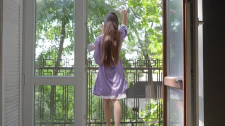 fürdőköpeny : young woman in silk bathrobe goes to the balcony of hotel with a cup and turns to the camera on background of green trees in the morning.