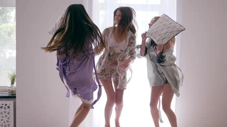 almofada : hen party, happy women friends jump with pillows on the bed in silk bathrobes at bedroom