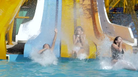 slayt : aquapark, cheerful Friends girls sliding on water slide and Dives into Poolside with Splashing on summer vacation