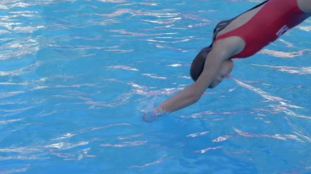 fejest ugrik : young woman in swimsuit jumping into clean blue pool and disappears under water close-up