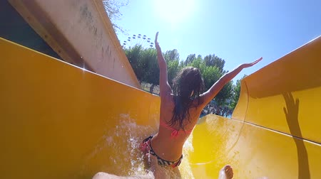 slayt : aquapark, Friends happily rolls on water slide and plunging into pool in summer water park on vacation close up