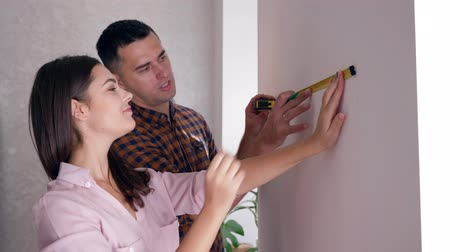 páska : apartment repair, young woman and man with tape measure in hand doing renovation in new housing close-up