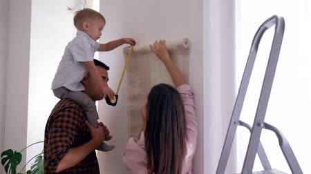 ремонт : family renovation in room, young mother and father with boy on shoulders glue new wallpaper on wall in flat