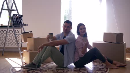 ремонт : housewarming, young couple enjoy new apartment and drinking tea sitting on floor among boxes with things after moving Стоковые видеозаписи