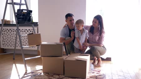 ремонт : merry family with small son enjoys new light home after repairs among cardboard boxes with things On floor