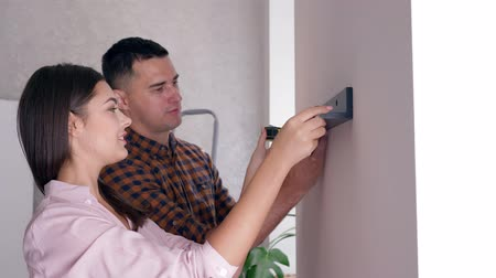 measure tape : repair in house, young couple with tape measure in hands hanging shelf on wall during renovation in new apartment Stock Footage