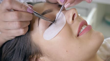 cílios : beauty salon, master of extension eyelash uses special glue and two tweezers close-up