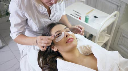 cílios : eyelash extension procedure, master combing lashes to a female client in a beauty salon