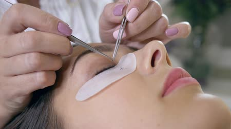 pinça : eyelash extension, professional master takes with forceps and stick artificial lashes on the womans eye close up Vídeos