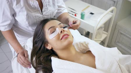 cílios : master combing eyelashes and prepares the client for the procedure in a beauty salon