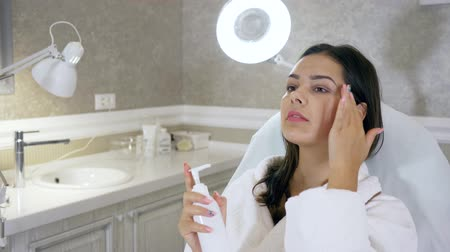 girl in robe : facial skin care, gorgeous girl uses a moisturizing face cream lying on the couch in the beauty salon Stock Footage