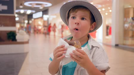 petite : Children food, cute happy kid into Hat eating chocolate doughnut in shopping mall close-up