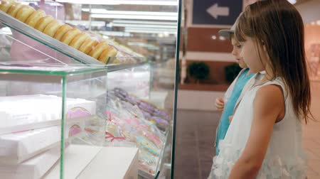 cruller : hungry child boy with girl near a glass showcase with cookies and donuts choose sweets close-up Stock Footage