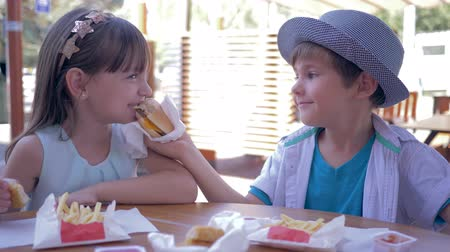 brothers : junk food, cute child boy feeding girlfriend burger in Street Cafe close-up Stock Footage