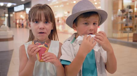 cruller : sweet tooth, happy children friends eat cookies and donut in shopping center close-up Stock Footage