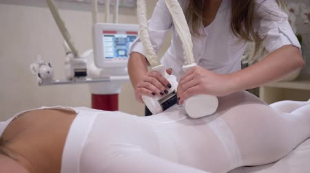 целлюлит : hardware massage, woman client in white suit lying on bed in a spa salon and enjoy anti-cellulite procedure on body