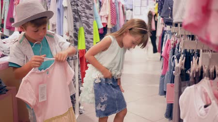 sisters : children on shopping, little buyers choose new fashionable clothes at expensive boutique during seasonal sale