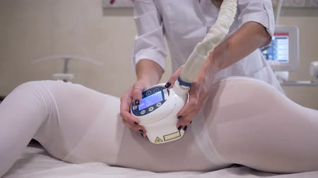 csökkenti a : beauty salon, female client reduces the volume of body with the help of a hardware massage