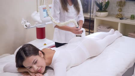 ass skin : body care with the help of LPG apparatus, lady client in a white hot suit is getting massage in cosmetology clinic
