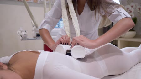 ass skin : care of figure, woman client lying on the bed in a beauty salon enjoying and receiving lipo massage procedure on body