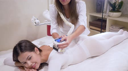 ass skin : care of the figure with the help of LPG apparatus, client girl in a white hot suit is getting massage on body in beauty salon Stock Footage