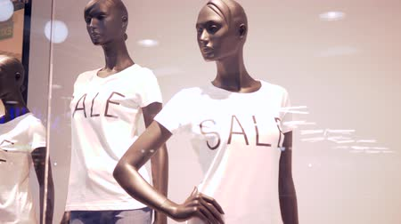 autumn discounts : seasonal sale, mannequin into clothing with inscription notice of discounts behind shop-window in fashion store Stock Footage