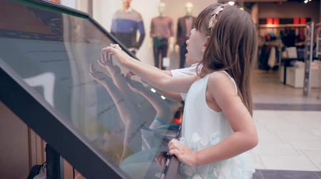 öz : self-service at mall, modern child boy and girl uses Information orientating system For search location of boutique at shopping center