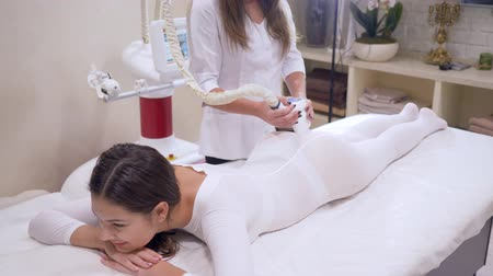 ass skin : LPG apparatus while working, young woman client in a white hot suit is getting treatment on body in cosmetology clinic