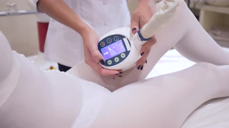 csökkenti a : hardware massage, girl client in a beauty salon reduces the volume of legs with the help of a procedure Stock mozgókép