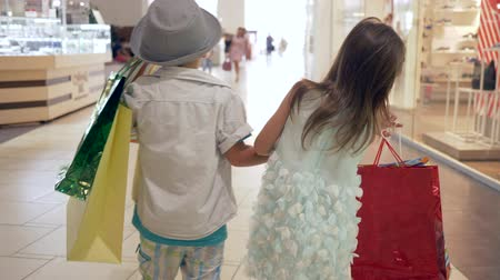 autumn discounts : shopping sales, little brother with sister with lots of packages walking together holding hands at mall after shopping on leisure