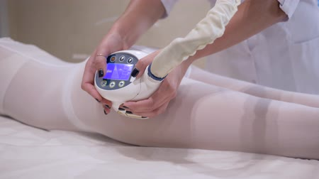 detém : massage and care for womens body in the beauty salon, female client in a white hot suit enjoys anticellulite procedure Vídeos