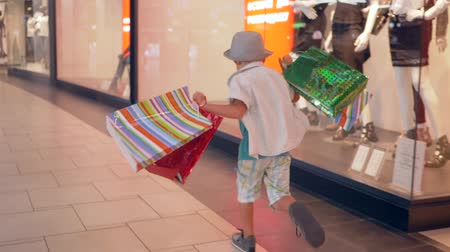 autumn discounts : autumn sale, fashion kid with shopping bags in hurry to get discount in boutiques at mall Stock Footage
