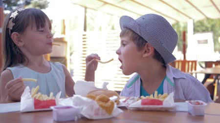 rejoices : children care, lovely kids feeding each other fast food sitting at table in street cafe closeup Stock Footage