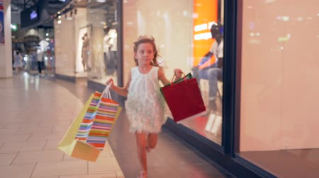 autumn discounts : happy shopper girl with paper bags in hurry to get discount in boutiques at mall