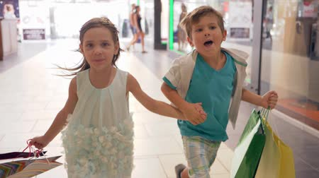 autumn discounts : joyful children with shopping bags run to make purchases at discounts during sales on black Friday at mall
