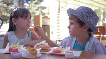 rejoices : junk meal for children, caring cute boy feeding girlfriend with french fries during lunch in street fast food cafe closeup