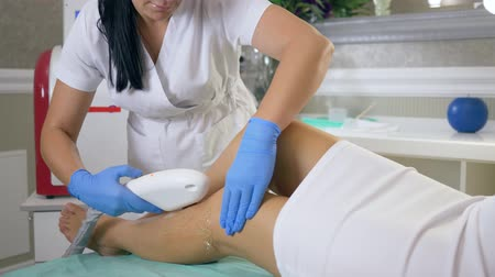 depilation laser : body care, beautician Doctor performing laser hair removal on female patient Feet in clinic close-up, Apparatus for epilation makes flares close-up Stock Footage