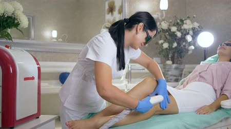 apparatus : care skin, professional cosmetologist into medical glasses does photoepilation on legs of lady client using laser machine in beauty Studio close-up Stock Footage