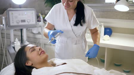 apparatus : Doctor beautician performing moisturizing skin patient girl with help of cosmetics apparatus with rejuvenating liquid in spa salon close-up