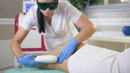 apparatus : female procedures, cosmetologist into medical glasses does depilation on legs of client woman using laser Apparatus in Beauty parlor close-up