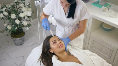 nourishing : relaxed woman enjoys rejuvenating procedures with help delivering nutrients to deeper layers of skin face in spa salon close-up Stock Footage